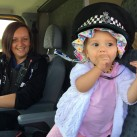 Butterfly Buckley-Ashford tries on a police hat for size while PCSO Hannah Parks looks on.