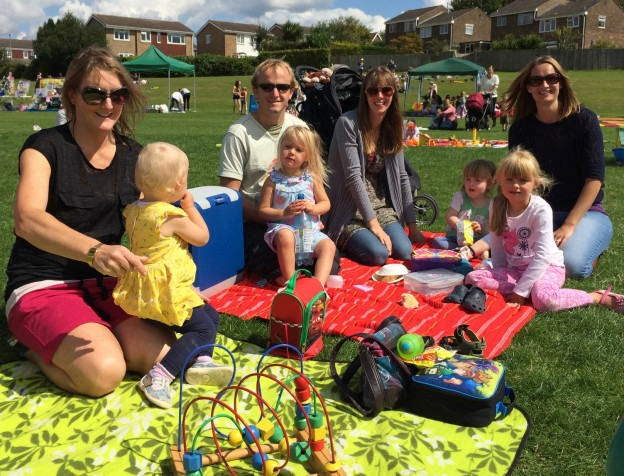 Families enjoy a picnic at the fun day.