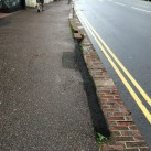 Even more bricks missing with the gap patched with tarmac.
