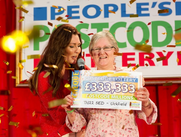 Sue Butler receives her cheque for £333,333, won in Postcode Lottery Millions.
