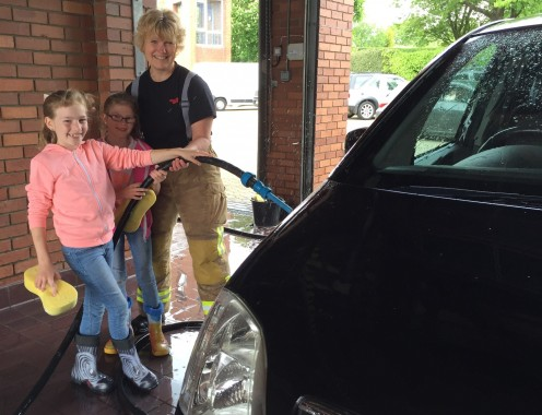 Uckfield firefighter Katinka Blauw helps Libby, eight, and Elyse, seven, Snelgrove clean a car during a car wash to raise funds to make an ill Uckfield child's dream come true.