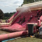 Working together - the Ridgewood Post Office team hold hands to slide into a mud pool.