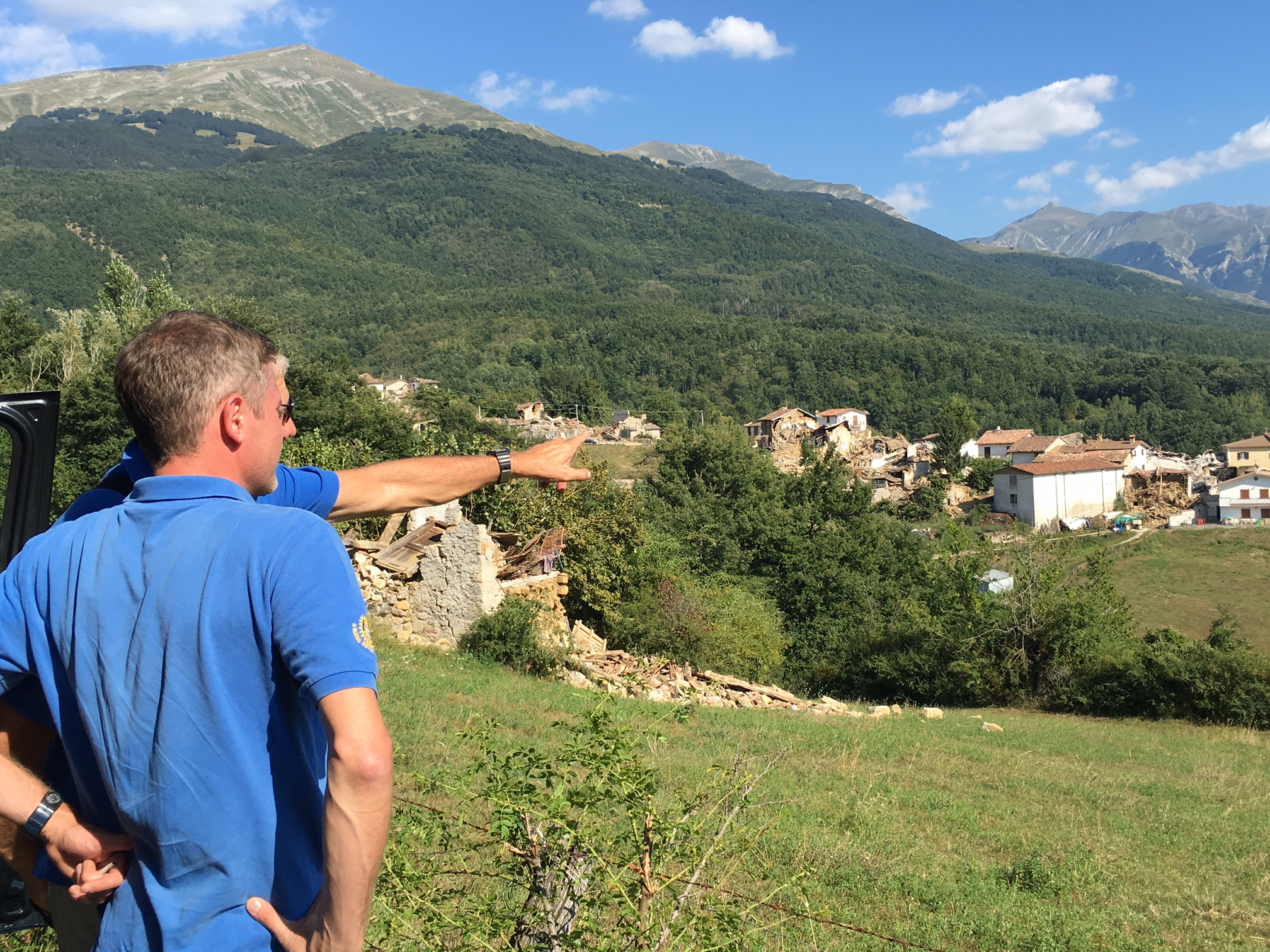 Italy quake - Phil and Ed, pointing to quake village