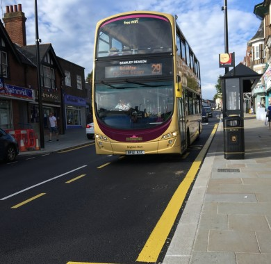A bus approaching a new bus stop in Uckfield High Street with its thicker yellow line