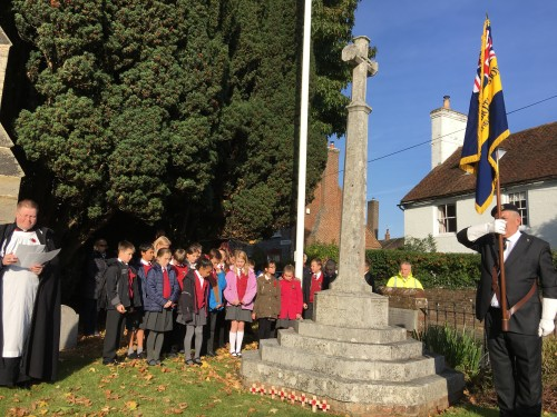 Fr John Wall and children of Hiolky Cross school observe the silence