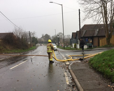 A firefighter clearing the hoses which had brought waiter across the Lewes Road to the scene of the blaze