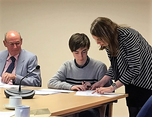 Callum Boyce signs the declaration of office watched by town clerk, Holly Goring, and Cllr Chris Macve