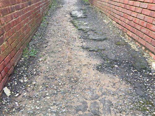 Broken tarmac on a twitten on the Manor Park Estate, Uckfield