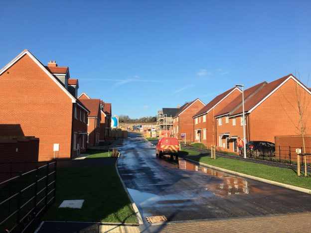 A Royal Mail delivery to new homes at Ridgewood Place with construction in the background